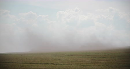 distante : Tractors Blowing Dust On Field Stock Footage