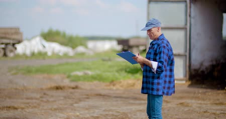 omologazione : Farmer gesturing while writing on clipboard against barn