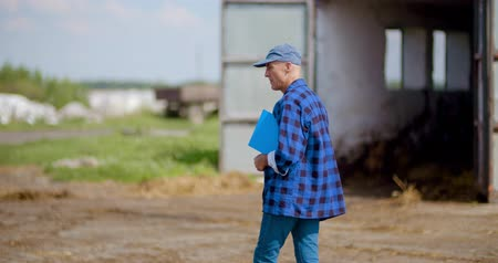 pet : Farmer gesturing while writing on clipboard against barn
