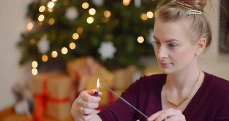 szikra : Young Woman Igniting Sparkler With Lighter At Home Stock mozgókép