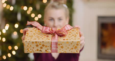 fejlövés : Young Woman Showing Her Christmas Gift At Home