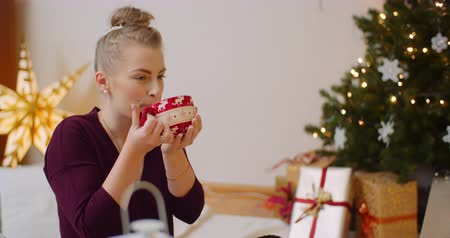 focus on foreground : Woman Drinking Coffee At Home During Christmas