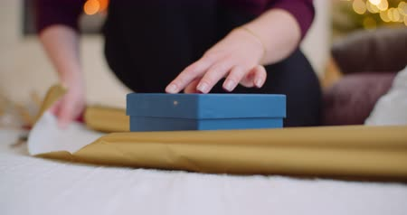 ラッピング : Woman Wrapping Christmas Present With Golden Gift Paper 動画素材