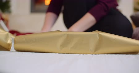 ラッピング : Woman Applying Tape Christmas Present With Golden Wrapping Paper 動画素材