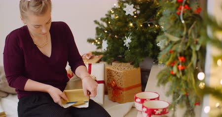 wrapping paper : Woman Wrapping Christmas Present By Fireplace At Home Stock Footage