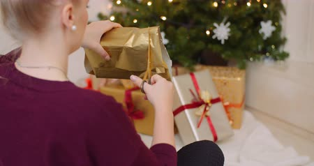 ラッピング : Woman Wrapping Christmas Present By Fireplace At Home 動画素材