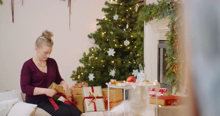 inpakpapier : Woman Wrapping Christmas Present By Fireplace At Home Stockvideo