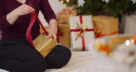 ラッピング : Attractive Woman Tying Ribbon On Gift Box At Home