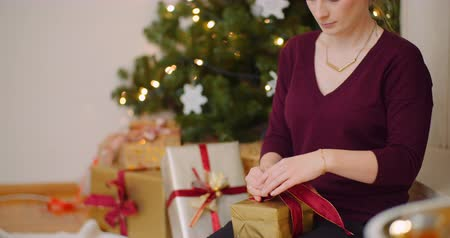 inpakpapier : Attractive Woman Tying Ribbon On Gift Box At Home