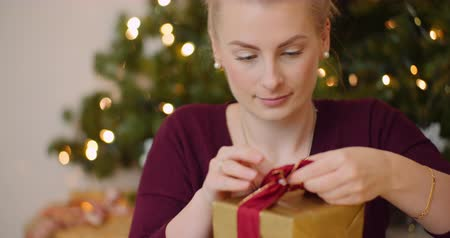 wrapping paper : Attractive Woman Tying Ribbon On Gift Box At Home
