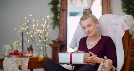 inpakpapier : Woman Holding Present While Sitting On Chair At Home Stockvideo