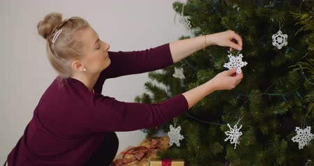 osvětlovací zařízení : Woman Decorating Christmas Tree With Ornaments And Lights