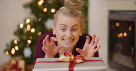 fejlövés : Playful Woman Opening Christmas Presents At Home