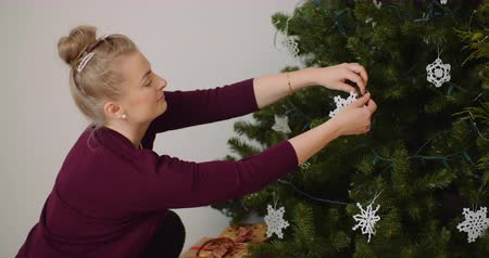 posicionamiento : Woman Decorating Christmas Tree With Ornaments And Lights