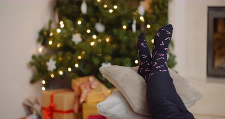 focus on foreground : Woman Relaxing With Legs On Cushions Against Christmas Tree Stock Footage