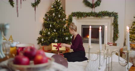 kandelaar : Young Woman Positioning Christmas Presents Under Tree