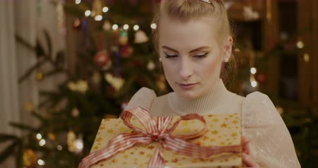 ajándékdobozban : Beautiful Young Woman Looking At Gift During Christmas