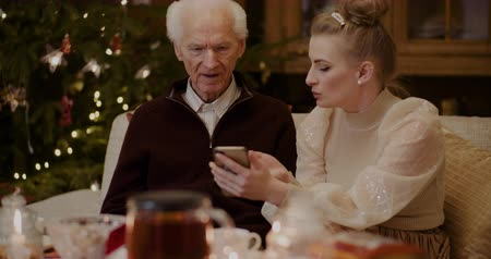nagyapa : Woman Teaching Grandfather To Use Smartphone In Christmas