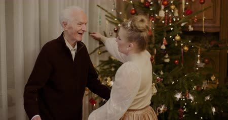 dziadkowie : Woman Giving Christmas Present To Grandfather At Home
