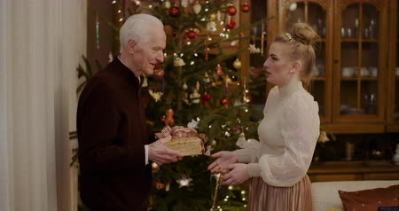 dospělí : Woman Giving Christmas Present To Grandfather At Home