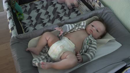 pažba : Newborn baby in diapers on a changing table near a pack n play. Dostupné videozáznamy