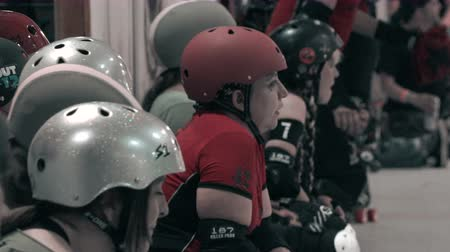 долл : Roller Derby Team Bench Shot. The roller girls from both teams taking a break during the action.