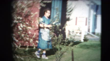 sinematografi : 8mm Vintage - 60s Lady and Blooming Apple Tree. This footage is a home movie made in the early 1960s on 8mm film. The footage was played on a B&H automatic loading projector and then transferred to 4k format using a video camera and mirrors. Color corre