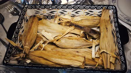 tradição : Homemade Tamales for Christmas Dinner. A tray of homemade tamales ready on the formal dining table for Christmas Dinner.