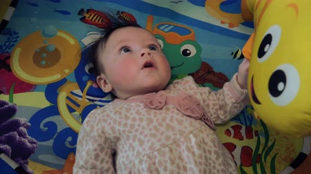 sassy : Baby on Aquatic Theme Playmat. A cute and happy baby is laying on an fun underwater type themed playmat.