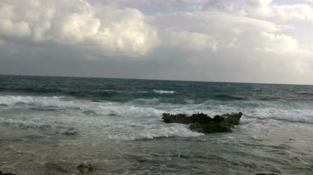 turistik : Perfect Loop Short Rocky Wave Break. Ocean waves clash over a shore reef with rocky structure as the wind blows and fluffy clouds loom afar. Stok Video
