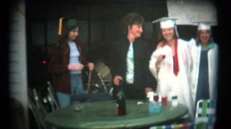 градация : 8mm Vintage High School Graduation Party.  A retro 8mm reeltoreel home movie film professional clean and captured in full 4k 3840x2160 UHD resolution plus footage restoration including color correction deinterlace deflicker. Стоковые видеозаписи