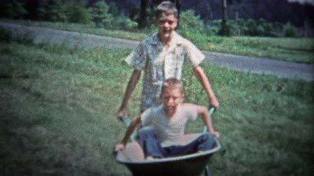 valóság : TENNESSEE, USA - 1953: Older brother pushing around kid in a wheelbarrow for summer fun.. Unique vintage 8mm film home movie professionally cleaned and captured in 4k 3840x2160 UHD resolution plus post processing including cinematic retro color correction