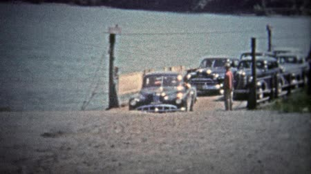 valóság : TENNESSEE, USA - 1954: Car ferry unloading at a rural spot along the Tennessee River.. Unique vintage 8mm film home movie professionally cleaned and captured in 4k 3840x2160 UHD resolution plus post processing including cinematic retro color correction, m Stock mozgókép