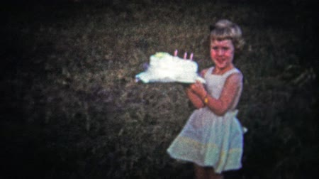 день рождения : TENNESSEE, USA - 1954: Woman handing child large birthday cake to pose with.. Unique vintage 8mm film home movie professionally cleaned and captured in 4k 3840x2160 UHD resolution plus post processing including cinematic retro color correction, manual spe