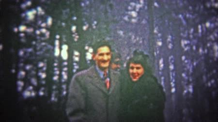 travessura : VERMONT, USA - 1947: Woman pranking couple by shaking tree snow on them.. Unique vintage 8mm film home movie professionally cleaned and captured in 4k 3840x2160 UHD resolution plus post processing including cinematic retro color correction, manual speed a