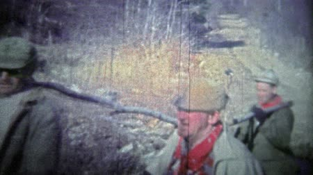 korszak : TENNESSEE, USA - 1952: Deer hunters clean and skin the kill out in the forest. . Unique vintage 8mm film home movie professionally cleaned and captured in 4k 3840x2160 UHD resolution plus post processing including cinematic retro color correction, manual