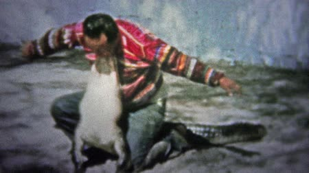 siyasi : FT. LAUDERDALE, USA - 1957: Native man wrestling alligator for the tourists as a strongman trick.. Unique vintage 8mm film home movie professionally cleaned and captured in 4k 3840x2160 UHD resolution plus post processing including cinematic retro color c
