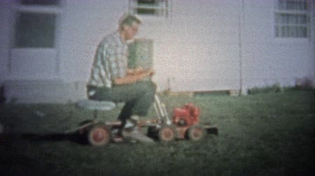 otec : NEW HAVEN, CONN. USA - 1957: Dad on new riding lawn mower towing kids on back.. Unique vintage 8mm film home movie professionally cleaned and captured in 4k 3840x2160 UHD resolution plus post processing including cinematic retro color correction, manual s Dostupné videozáznamy