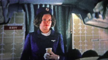 korszak : CHICAGO - 1966: Stewardess on an international flight on an airplane bound for Europe. . Unique vintage 8mm film home movie professionally cleaned and captured in 4k 3840x2160 UHD resolution plus post processing including cinematic retro color correction, Stock mozgókép