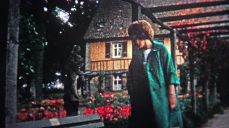 político : HAMBURG, GERMANY - 1966: Women walking through red flower conservatory garden during the height of the bloom.. Unique vintage 8mm film home movie professionally cleaned and captured in 4k 3840x2160 UHD resolution plus post processing including cinematic r Vídeos