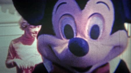 DISNEYLAND, CALIFORNIA, USA - 1956: Mickey Mouse entertaining kids in costume as the park grew. Original vintage 8mm home movie film professionally cleaned and captured in 4k 3840x2160 UHD resolution plus post processing including cinematic retro color co Wideo