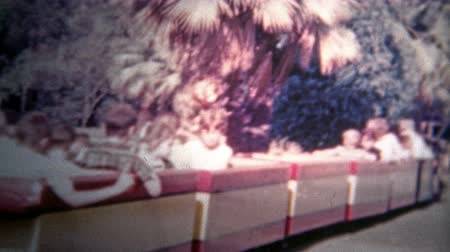 valóság : DISNEYLAND, CALIFORNIA, USA - 1956: Kids on the Disney train as it pulls away from dad. Original vintage 8mm home movie film professionally cleaned and captured in 4k 3840x2160 UHD resolution plus post processing including cinematic retro color correction Stock mozgókép