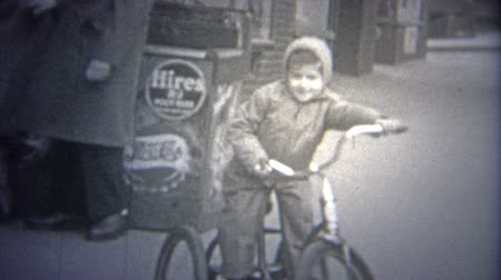 korszak : NEW YORK CITY - 1946: Boy riding bike on streets past a local urban news-stand. Original vintage 8mm home movie film professionally cleaned and captured in 4k 3840x2160 UHD resolution plus post processing including cinematic retro color correction, deflic