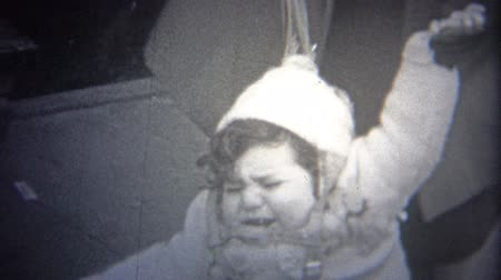 archívum : NEW YORK CITY - 1946: Mom has a safety protection harness leash on baby . Original vintage 8mm home movie film professionally cleaned and captured in 4k 3840x2160 UHD resolution plus post processing including cinematic retro color correction, deflickering