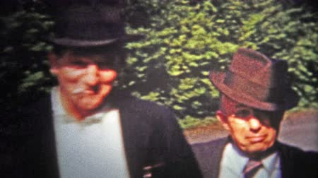 archívum : CHATTANOOGA, USA - 1953: Single men of the day wearing fedora hats and smoking. Original vintage 8mm home movie film professionally cleaned and captured in 4k 3840x2160 UHD resolution plus post processing including cinematic retro color correction, deflic Stock mozgókép