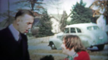 archívum : CHATTANOOGA, USA - 1954: Man teasing little girl outside of the residential area. Original vintage 8mm home movie film professionally cleaned and captured in 4k 3840x2160 UHD resolution plus post processing including cinematic retro color correction, defl Stock mozgókép