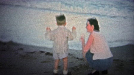 valóság : NANTUCKET. USA - 1957: Kid sees ocean waves for the first time while safely on the beach, gets scared. . Unique vintage 8mm film home movie professionally cleaned and captured in 4k 3840x2160 UHD resolution plus post processing including cinematic retro c