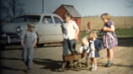 sinematografi : 8mm Vintage 1952 Farm Kids Pulling Wagon. Iowa, USA. Stok Video