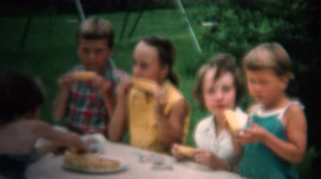 sinematografi : 8mm Vintage 1954 Kids Eating Roasted Corn On The Cob. Iowa, USA.