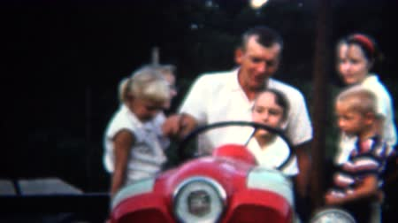 sinematografi : 8mm Vintage 1954 Dad Letting Daughter Drive Family Farm Tractor. Iowa, USA. Stok Video